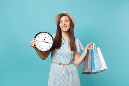 Portrait beautiful young caucasian woman in summer dress, straw hat holding packages bags with purchases after shopping, round clock isolated on blue pastel background. Copy space for advertisement