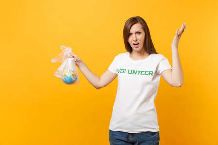 Woman portrait in white t-shirt written inscription green title volunteer hold in plastic bag Earth world globe isolated on yellow background. Voluntary free assistance help, charity grace concept