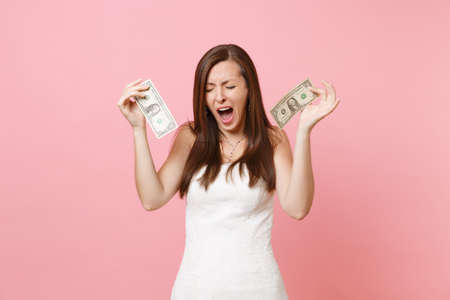 Portrait of dissatisfied bride woman in white wedding dress crying holding one dollar bills isolated on pastel pink background. Lack of money. Organization of wedding celebration concept. Copy space