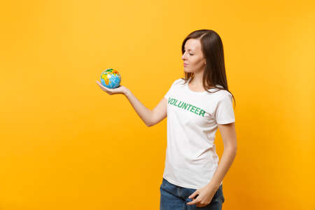 Portrait of woman in white t-shirt with written inscription green title volunteer hold in palms Earth world globe isolated on yellow background. Voluntary free assistance help, charity grace concept Stock Photo