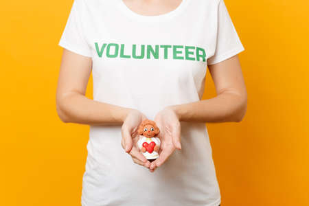 Cropped photo of woman in white t-shirt written inscription green title volunteerhold little angel in palms isolated on yellow background. Voluntary free assistance help, charity grace work concept