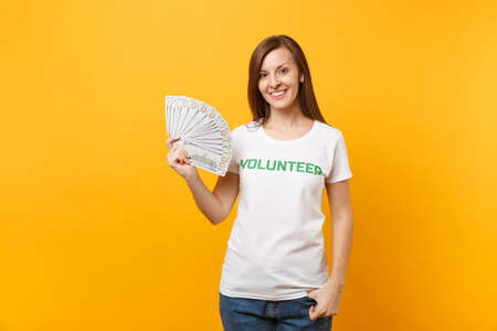 Woman in white t-shirt with written inscription green title volunteer hold lots dollars banknotes, cash money isolated on yellow background. Voluntary free assistance help, charity grace work concept Stok Fotoğraf