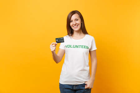 Portrait of young woman in white t-shirt with written inscription green title volunteer hold credit bank card isolated on yellow background. Voluntary free assistance help, charity grace work concept
