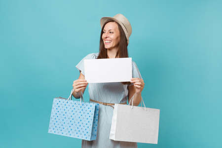 Portrait woman in summer dress, straw hat holding packages bags with purchases after shopping, empty blank Say cloud, speech bubble card isolated on blue pastel background. Copy space advertisement.