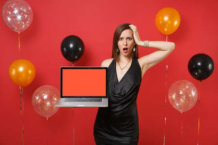 Irritated woman in black dress putting hand on head hold laptop pc computer with blank black empty screen on bright red background air balloons. Happy New Year, birthday mockup holiday party concept