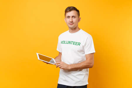Portrait man in white t-shirt with written inscription green title volunteer using typing tablet pc computer isolated on yellow background. Voluntary free assistance help, charity grace work concept Stock Photo