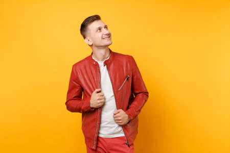 Portrait vogue confident handsome young man 25-30 years in red leather jacket, t-shirt stand isolated on bright trending yellow background. People sincere emotions lifestyle concept. Advertising area Stock Photo