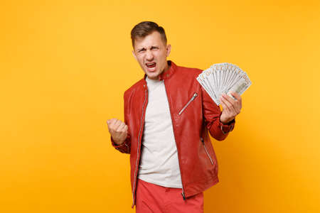 Portrait vogue fun crazy young man in red leather jacket t-shirt holding lots of banknotes, cash money isolated on bright trending yellow background. People lifestyle concept. Advertising area Stok Fotoğraf