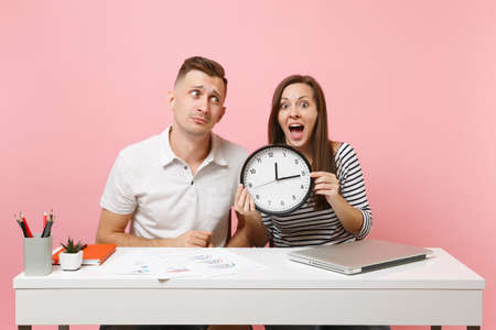 Two young fun shocked business woman man colleagues sit work at white desk with clock, laptop isolated on pastel pink background. Achievement career concept. Copy space advertising, youth co working