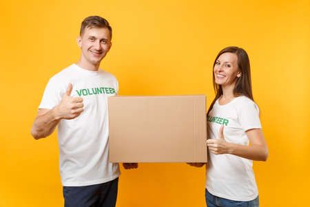 Colleagues couple in white t-shirt with written inscription green volunteer hold cardboard box donations isolated on yellow background. Voluntary free assistance help, charity grace teamwork concept