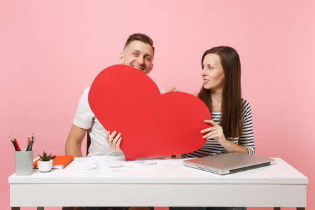 Two young fun business woman man colleagues sit work at white desk with big red heart, laptop isolated on pastel pink background. Achievement career concept. Copy space advertising, youth co working 写真素材