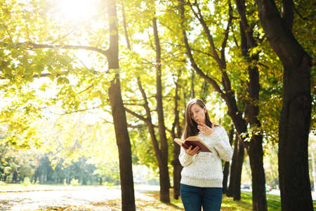 The beautiful happy smiling brown-haired woman in white sweater standing with a red book in fall city park on a warm day. Autumn golden leaves. Reading concept.