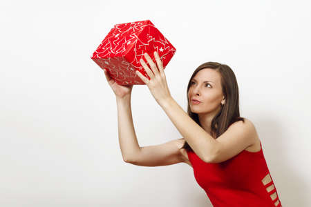 Interested engaged young woman dressed in red dress holds gift box, thinks that she was given on white background.