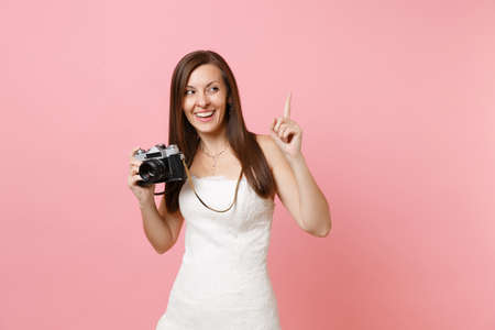 Happy bride woman in wedding dress pointing index finger up holding retro vintage photo camera choosing staff photographer isolated on pink background. Wedding to do list. Organization of celebration