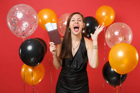 Overjoyed young woman in black dress holding passport, boarding pass tickets, spreading hands, screaming on bright red background air balloons. Happy New Year, birthday mockup holiday party concept Archivio Fotografico