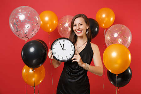Smiling young woman in little black dress celebrating, holding round clock on bright red background air balloons. St. Valentine's, Women's Day, Happy New Year, birthday mockup holiday party concept 版權商用圖片