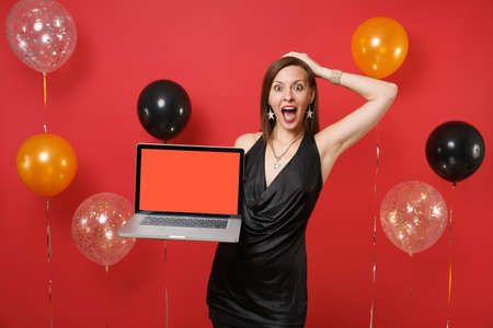 Excited girl in black dress putting hand on head holding laptop pc computer with blank black empty screen on bright red background air balloons. Happy New Year, birthday mockup holiday party concept