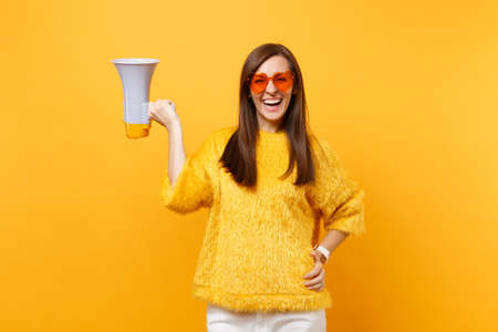 Portrait of cheerful attractive young woman in fur sweater orange heart eyeglasses holding megaphone isolated on bright yellow background. People sincere emotions, lifestyle concept. Advertising area Stockfoto