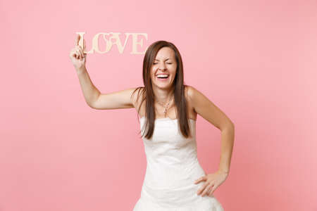 Portrait of laughing bride woman with closed eyes in white wedding dress standing with arm akimbo holding wooden word letters love isolated on pastel pink background. Wedding celebration. Copy space Stock Photo