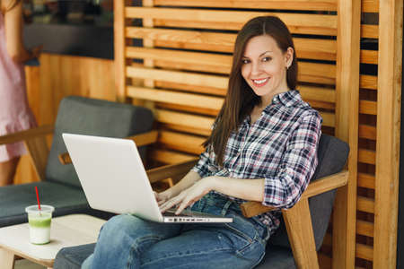 Woman in outdoors street summer coffee shop wooden cafe sitting in casual clothes, working on modern laptop pc computer, relaxing during free time. Mobile Office. Lifestyle freelance business concept Stock Photo