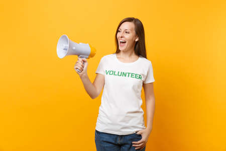 Woman portrait in white t-shirt written inscription green title volunteer scream in public address megaphone isolated on yellow background. Voluntary free assistance help, charity grace work concept
