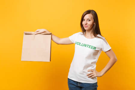 Portrait of woman in white t-shirt written inscription green title volunteer hold blank craft paper bag for takeaway isolated on yellow background. Voluntary free assistance charity grace concept Stock Photo