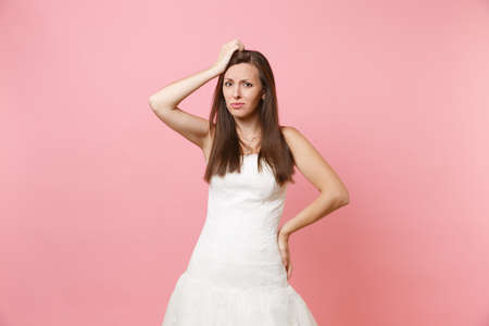 Portrait of concerned puzzled bride woman in white wedding dress stand have problem keeping hand on head isolated on pink pastel background. Wedding celebration concept. Copy space for advertisement