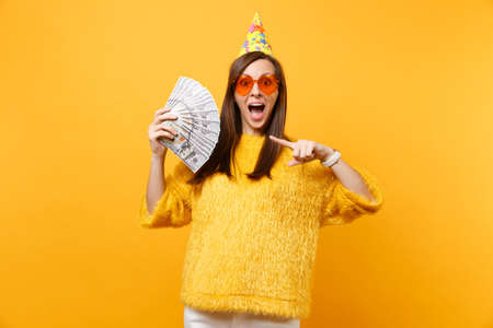 Excited young woman in orange heart glasses and birthday hat pointing index finger on bundle lots of dollars cash money, celebrating isolated on yellow background. People sincere emotions, lifestyle