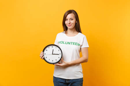 Portrait of woman in white t-shirt with written inscription green title volunteer hold round clock isolated on yellow background. Voluntary free assistance help, charity grace work time concept.