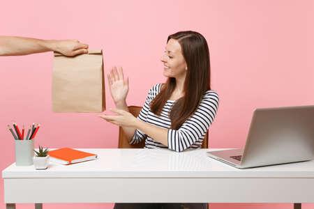 Kobieta bierze brązową przezroczystą pustą pustą papierową torbę rzemiosła, pracuje w biurze z laptopem pc na białym tle na różowym tle. Usługa kurierska dostarczająca produkty spożywcze ze sklepu lub restauracji do biura.