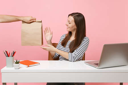 Woman taking brown clear empty blank craft paper bag, work at office with pc laptop isolated on pink background. Food products delivery courier service from shop or restaurant to office. Archivio Fotografico - 109689517