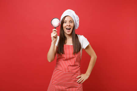 Housewife female chef cook or baker in striped apron white t-shirt toque chefs hat isolated on red wall background. Housekeeper woman hold look through magnifying glass. Mock up copy space concept