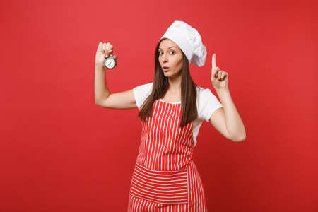 Housewife female chef cook or baker in striped apron, white t-shirt, toque chefs hat isolated on red wall background. Smiling woman hold in hand retro alarm clock hurry up. Mock up copy space concept