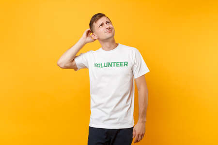 Portrait of displeased irritated young man in white t-shirt with written inscription green title volunteer isolated on yellow background. Voluntary free assistance help, charity grace work concept