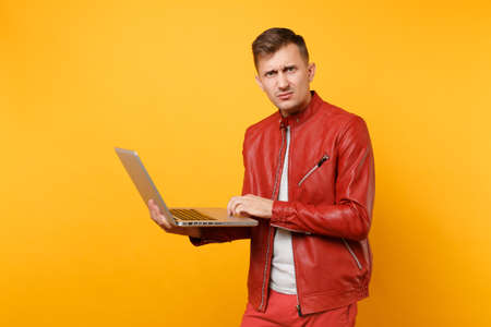 Portrait vogue fun handsome young man in red leather jacket, t-shirt using laptop pc tablet isolated on bright trending yellow background. People sincere emotions lifestyle concept. Advertising area