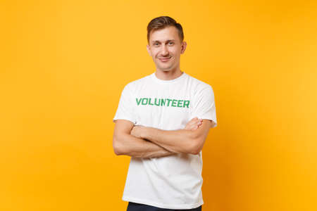 Portrait of happy smiling satisfied young man in white t-shirt with written inscription green title volunteer isolated on yellow background. Voluntary free assistance help, charity grace work concept
