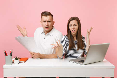 Two young angry business woman man colleagues sit work at white desk with contemporary laptop isolated on pastel pink background. Achievement career concept. Copy space advertising, youth co working