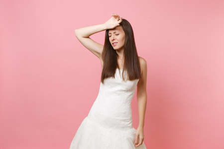 Portrait of exhausted bride woman in white wedding dress keeping hand on forehead tired of preparing for wedding isolated on pink background. Wedding celebration concept. Copy space for advertisement