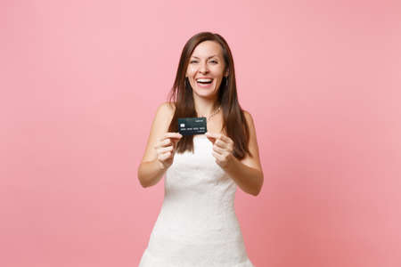 Portrait of laughing bride woman in white wedding dress showing credit card on camera isolated on pink pastel background. Organization of wedding celebration concept. Copy space for advertisement