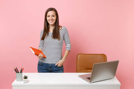 Young successful woman in casual clothes holding notebook work standing near white desk with contemporary pc laptop isolated on pastel pink background. Achievement business career concept. Copy space