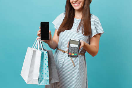 Portrait woman in dress, hat holding packages bags with purchases after shopping, wireless modern bank payment terminal to process and acquire credit card payments isolated on blue pastel background