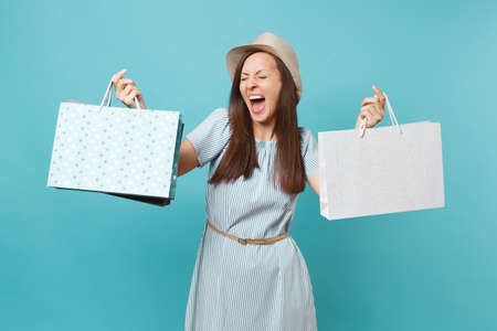 Portrait excited smiling beautiful caucasian woman in summer dress, straw hat holding packages bags with purchases after shopping isolated on blue pastel background. Copy space for advertisement Banco de Imagens