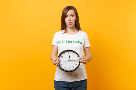 Portrait of woman in white t-shirt with written inscription green title volunteer hold round clock isolated on yellow background. Voluntary free assistance help, charity grace work time concept. Banque d'images - 109771511