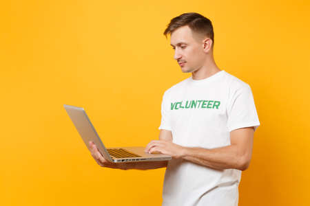 Portrait man in white t-shirt with written inscription green title volunteer using typing laptop pc computer isolated on yellow background. Voluntary free assistance help, charity grace work concept