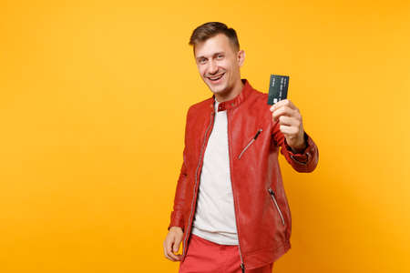 Portrait vogue smiling handsome young man in red leather jacket t-shirt hold bank credit card isolated on trending yellow background. People sincere emotions lifestyle concept. Advertising area