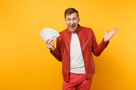 Portrait vogue handsome young man in red leather jacket, t-shirt holding lots of dollars banknotes cash money isolated on bright trending yellow background. People lifestyle concept. Advertising area