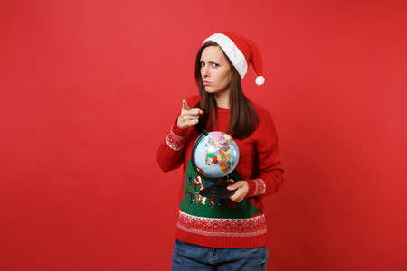 Strict young Santa girl in Christmas hat holding world globe pointing index finger on camera isolated on red wall background. Happy New Year 2019 celebration holiday party concept. Mock up copy space Foto de archivo