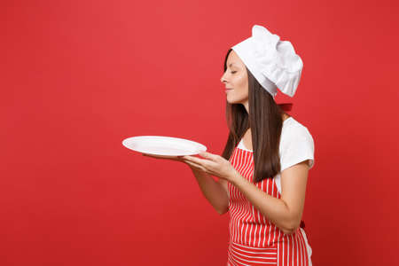 Housewife female chef cook or baker in striped apron white t-shirt, toque chefs hat isolated on red wall background. Woman hold empty blank round plate with place for food. Mock up copy space concept