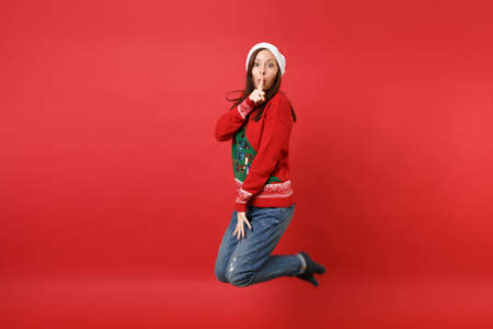 Pretty secret young Santa girl jumping, saying hush be quiet with finger on lips, shhh gesture isolated on red background. Happy New Year 2019 celebration holiday party concept. Mock up copy space Stockfoto