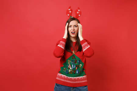 Perplexed young Santa girl in knitted sweater, fun decorative deer horns putting hands on head isolated on red background. Happy New Year 2019 celebration holiday party concept. Mock up copy space 版權商用圖片